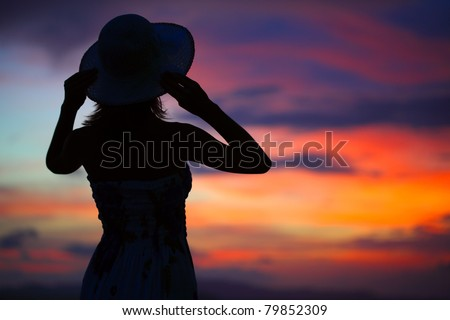 Silhouette of woman in hat on colorful and vivid sunset background