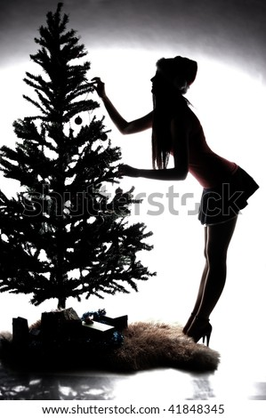 Silhouette of woman in mini decorating christmas tree - stock photo