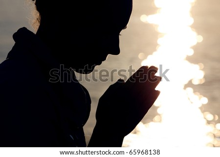 Silhouette of woman in  type, which sits ashore  and prays fold arms