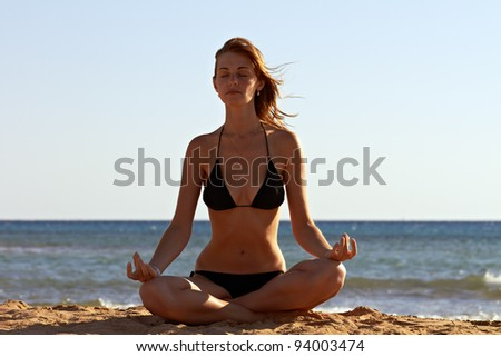 Silhouette of woman in yoga lotus meditation position back to seaside