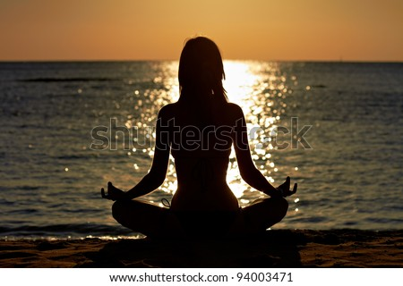 Silhouette of woman in yoga lotus meditation position front to seaside