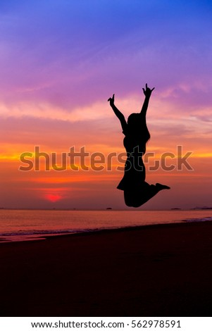Silhouette of woman jumping with hands up and showing I LOVE YOU sign on the sea beach at sunset