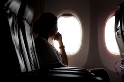 Silhouette of woman looks out the window of an flying airplane. Passenger on the plane resting beside the window.