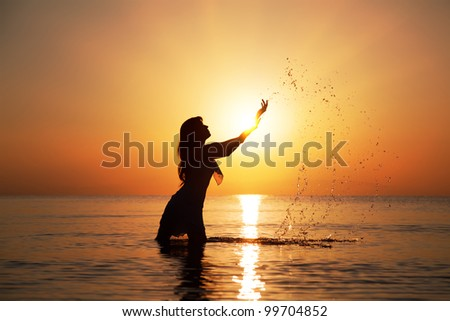 Silhouette of woman making splashes in the rays of the rising sun. Horizontal photo - stock photo