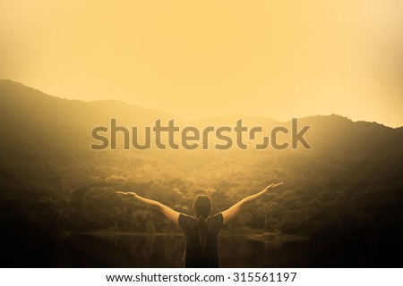 Silhouette of woman on a summit with upraised arms on the top mountain with the sunset, Praise for GOD.
