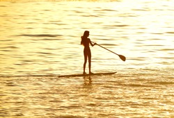 silhouette of woman paddleboarding at sunset, malibu, california, recreation sport paddling ocean beach surf orange sunlight reflection hue on water