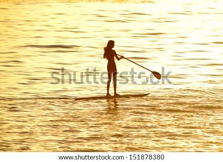 Silhouette Of Woman Paddleboarding At Sunset, Malibu, California, Recreation Sport Paddling Ocean Beach Surf Orange Sunlight Reflection Hue On Water