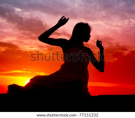 Silhouette of woman performs as a dancer during sunset