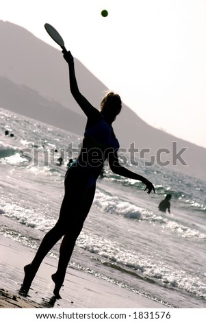 Silhouette of woman playing beach tennis at sunset