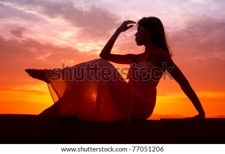 Silhouette of woman posing on the boat during sunset
