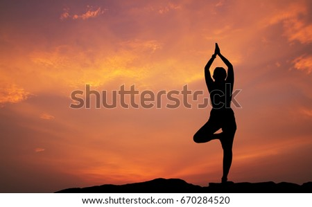 Silhouette of woman practicing yoga at sunset #670284520