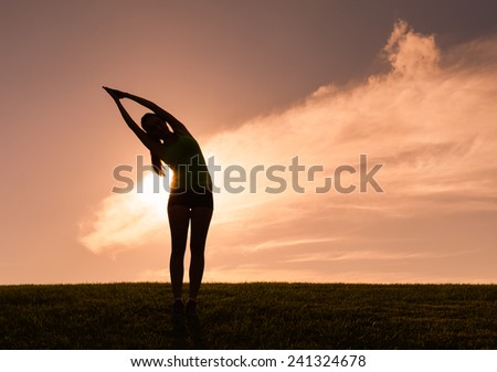 Silhouette of woman practicing yoga in the park