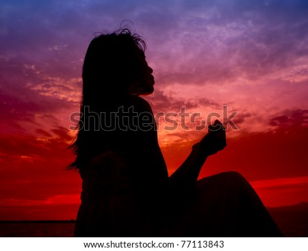 silhouette of woman praying during sunset
