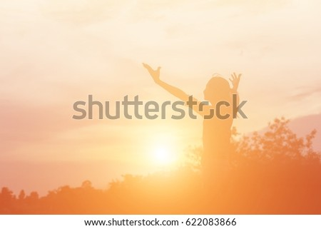 Silhouette of woman praying over beautiful sky background #622083866