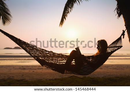silhouette of woman relaxing in hammock on the beach