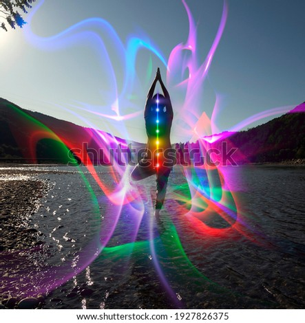 Silhouette of woman sits in a Upward Salute pose on beach sunset view, glowing seven all chakra. Kundalini energy. girl practicing yoga meditation outdoors