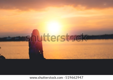 Silhouette of woman sitting riverside and beautiful sunset background.