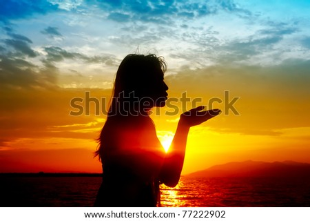 Silhouette of woman spreads out his hands during colorful sunset