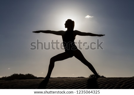 Silhouette of woman standing in asana on sandy coastline against back lit
