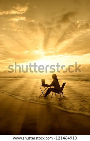 Silhouette of woman study on the beach under beautiful rays of light