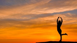 Silhouette of woman with arms raised in a ballerina position, on a very beautiful sunset background. An image that conveys positivism.