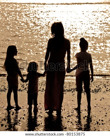 Silhouette of woman with children on sea beach