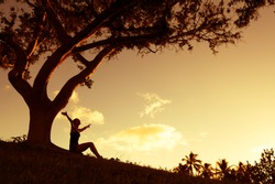 Silhouette of woman with hands raised into sunset