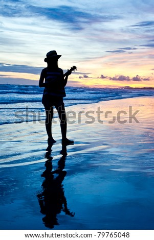 Silhouette of woman with ukulele on the sunset beach