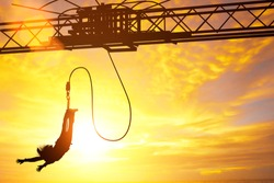 Silhouette of women jumping down bungee jump sport in sunset and light flare