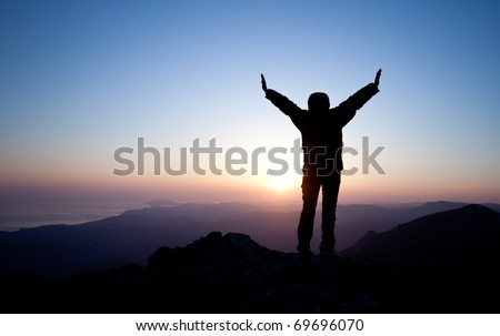 silhouette of women meeting sunrise on the top of mountain