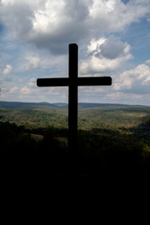 silhouette of wooden cross on top of a mountain close to heaven