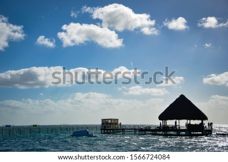 Silhouette of wooden shelter hut in the middle of the sea #1566724084