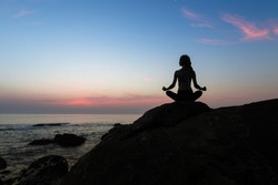 Silhouette of yoga woman sit at Lotus position on the shore of ocean at amazing twilight.
