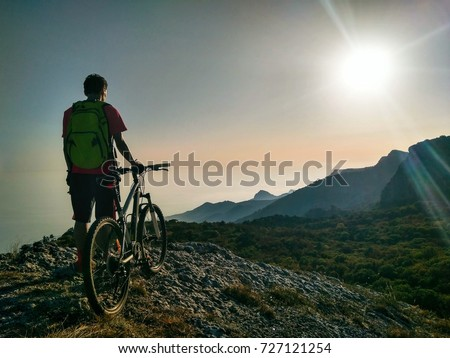 Silhouette of young active man with bicycle standing and looking forward at mountains panoramic background #727121254