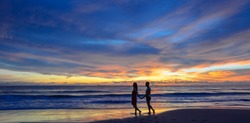 silhouette of young Asian couple during sunset, photo taken on Lanta island beach, Krabi, Thailand.