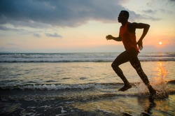 silhouette of young athletic and fit african american sport man doing running workout on sunset at the beach training hard jogging barefoot in healthy lifestyle concept