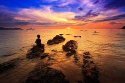 silhouette of young boy show the love hand and standing on rock in the sea with sunset sky, long speed exposure,Tarn-khu beach at Trat, Thailand