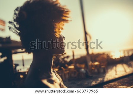 Silhouette of young Brazilian girl with curly afro hair illuminated by orange light looking on coastline while standing on embankment on windy summer evening, with beach cafe in defocused background