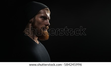 Photo of Silhouette of young confident handsome bearded man hipster wearing black knit hat. Studio shot on dark background Image with free copy space