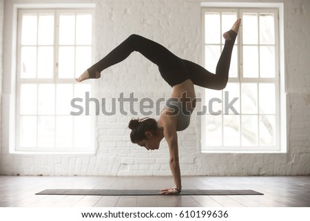 Silhouette of young cool attractive yogi woman practicing yoga concept, standing in Adho Mukha Vrksasana exercise, Downward facing Tree pose, working out, wearing sportswear bra and pants, full length stock photo