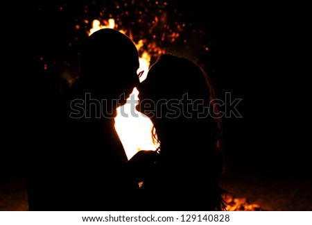 Silhouette of young couple about to kiss against fire in the night