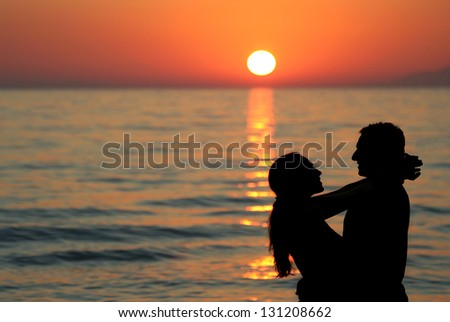 Silhouette of young couple at the sea holding each other