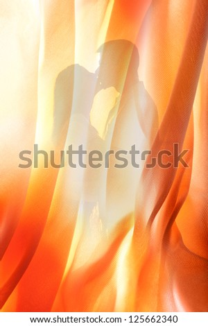 Silhouette of young couple kissing behind curtain.