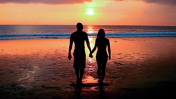Silhouette of young couple walking on beach at sunset