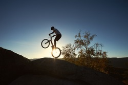 Silhouette of young cyclist balancing on back wheel on trial bicycle. Sportsman biker making trick on the edge of big rock on the top of mountain at sunset. Concept of extreme sport active lifestyle