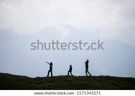 Silhouette of young family hiking in mountains