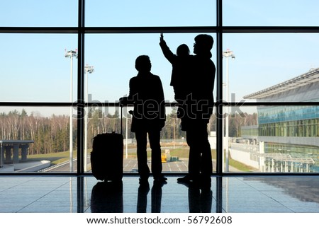 silhouette of young family with luggage standing near window in airport