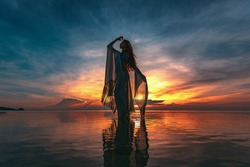 silhouette of young fashionable woman standing in water on the beach at sunset