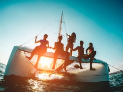 Silhouette of young friends chilling in private catamaran boat - Group of people making tour ocean trip - Alternative travel vacation during Coronavirus outbreak - Focus on left girl - Water on camera