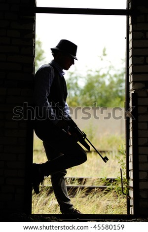 silhouette of young gangster with rifle